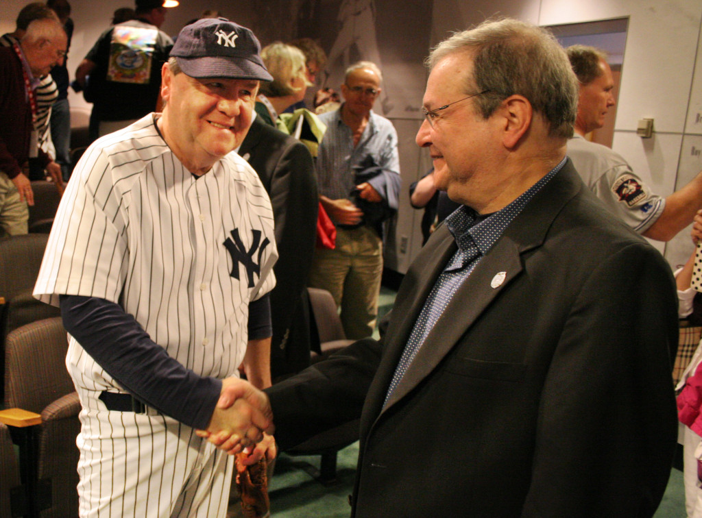 """Author, baseball historian and SUNY Oneonta grad Marty Appel, right, was on hand today at the Baseball Hall of Fame, promoting his book """"Pinstripe Empire,"""" and speaking about his experiences in baseball. Here, Appel shakes hands with Steve Folven, a Babe Ruth impersonator at the Hall of Fame for the opening of the Babe Ruth Exhibit. (Ian Austin/allotsego.com)"""