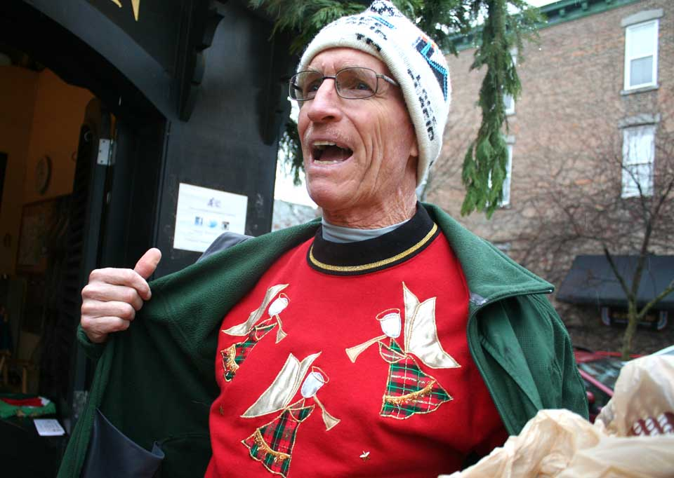 A disappointed Jim Hill, Cooperstown, nonetheless shows off his ugly sweater at Pioneer Park this morning on learning Cooperstown Chamber executive director Matt Hazzard, fearful of icy conditions, delayed 12:30's Ugly Sweater Race for a week, hoping for more cooperative weather on the 13th.  However, Bourbon & Branch will be performing 1:30-3 p.m. at the Smithy Pioneer Gallery those in the festive mood.  (Jim Kevlin/allotsego.com)