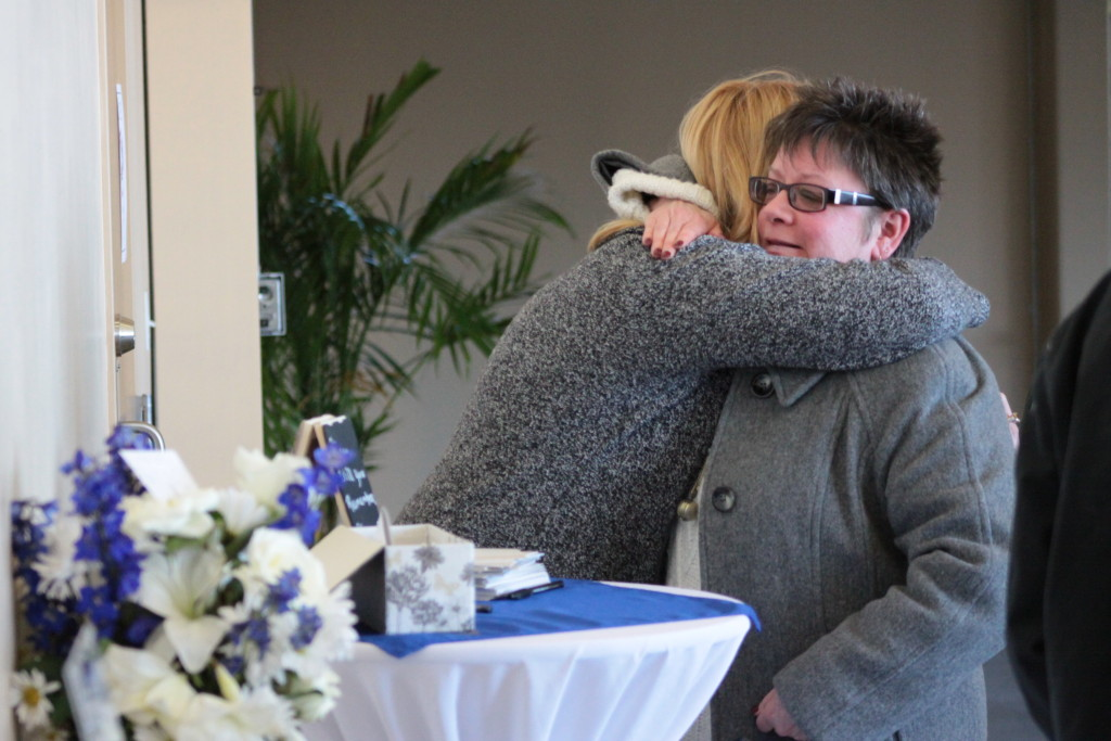 Friends and family of the late Kellie Place gathered in the Foothills Atrium where a memorial service was held Sunday afternoon. Here, after writing memories of Kellie for the family, Johnna Peachin embraces her friend Rachel Jessup in mourning.