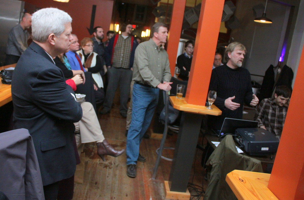 Oneonta City Manager Martin Murphy, left and Mayor Russ Southard listen to Wayne Carrington, owner of the B-Side Ballroom explain the new website for Destination Oneonta (Formally Main Street Oneonta) at the annual meeting hosted by the Roots Brewing Company this evening.  The website, when launched, will serve as a hub for Oneonta businesses, restaurants and hotels. (Ian Austin/ allotsego.com)
