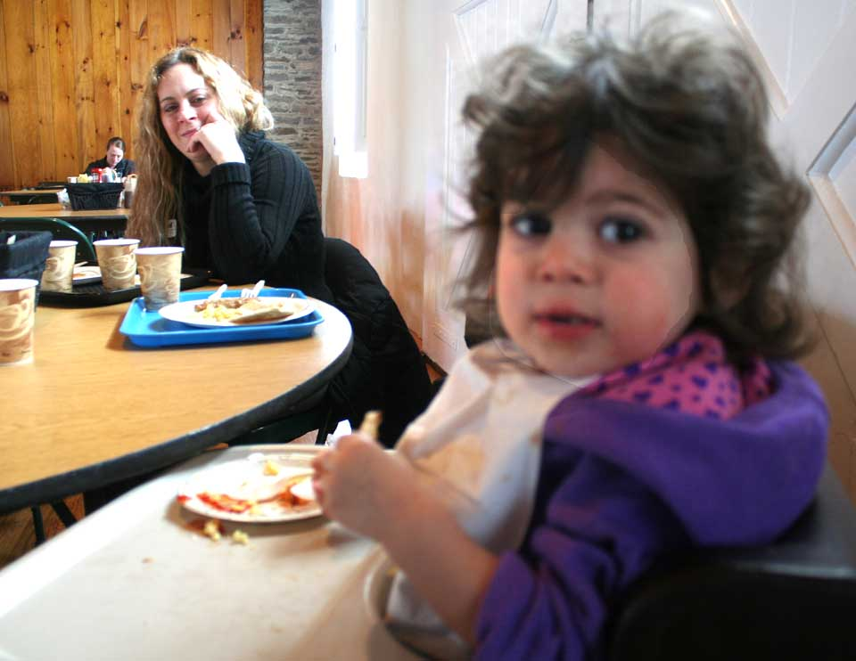 Under the watchful eye of mom Christine, Lauren Isgro, 2, tucks into her breakfast this morning at The Farmers' Museum's first Sugaring Off Sunday, a sign of spring around here.  Volunteers are serving eggs, pancakes and other goodies until 1 p.m. (Jim Kevlin/allotsego.com)