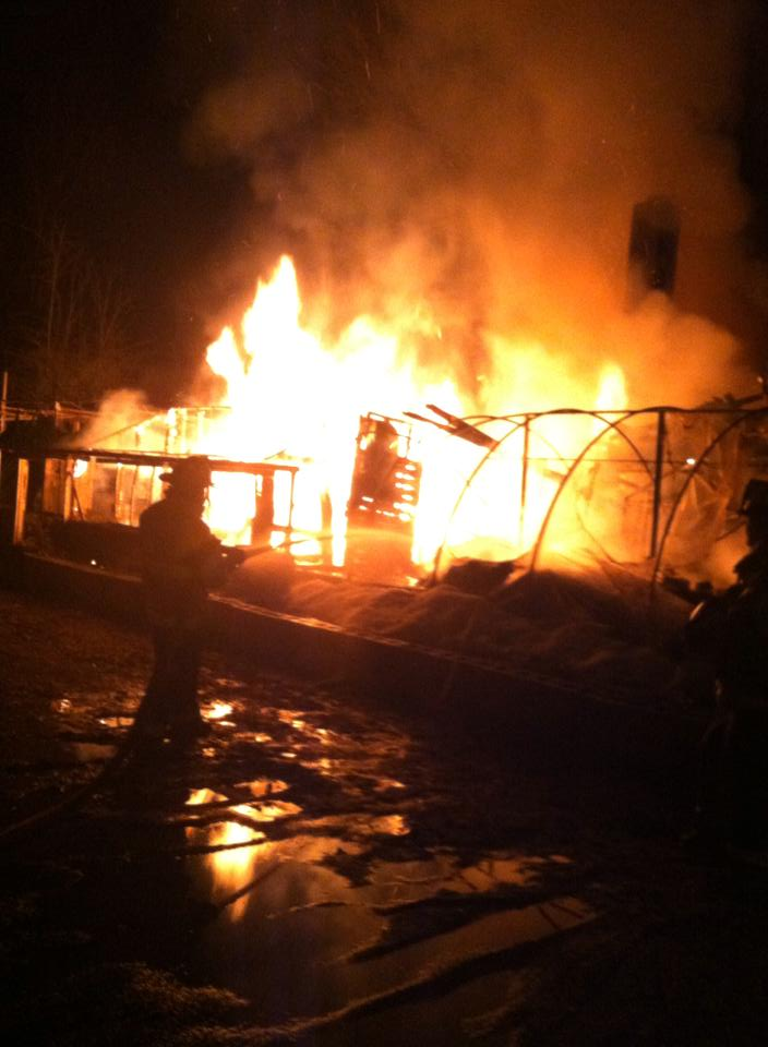 """A 100-year-old greehouse behind Mohican Flowers, Cooperstown, is consumed in """"a ball of flame"""" last evening.  The fire broke out at about 10:30 p.m.  (Photo by Bill Waller)"""