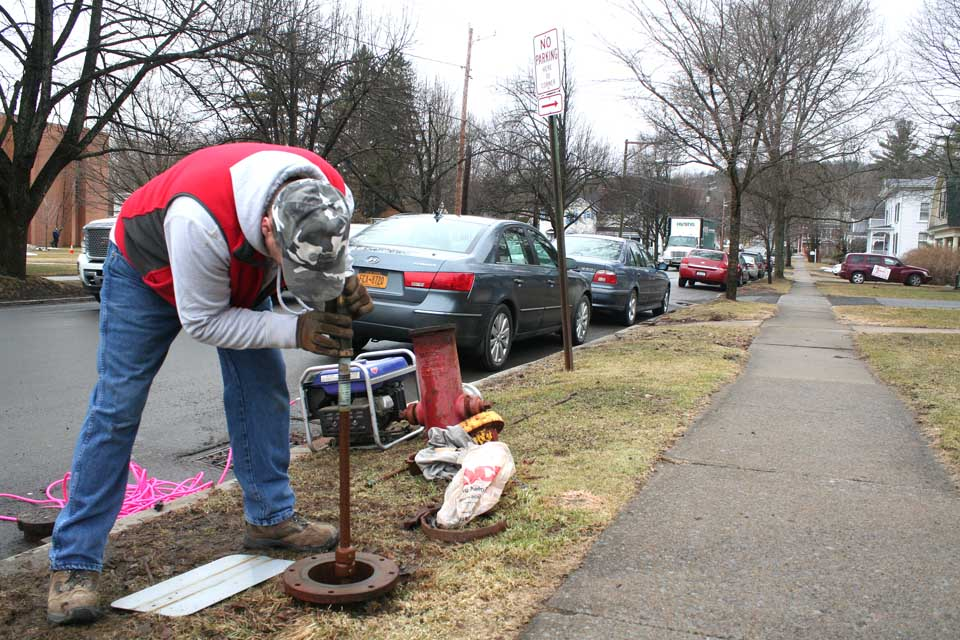 Dennis Elliott of the village DPW this morning replaces the snapped flange on the hydrant at Main and Nelson.  (Jim Kevlin/allotsego.com)