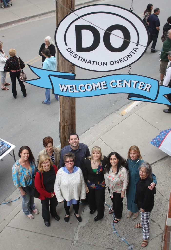 The first Fabulous First Friday of 2015 returned to Oneonta, with the opening of the new Destination Oneonta office at 2 Dietz St. Here, D.O. board members Julia Goff, Nancy Scanlon, Colleen Brannan, Rachel Jessup, Tim Masterjohn, Kristen Oehl, Louisa Montanti, Caroline Lewis and Sophie Richardson pose for a group photo beneath the new sign (Ian Austin/ allotsego.com)