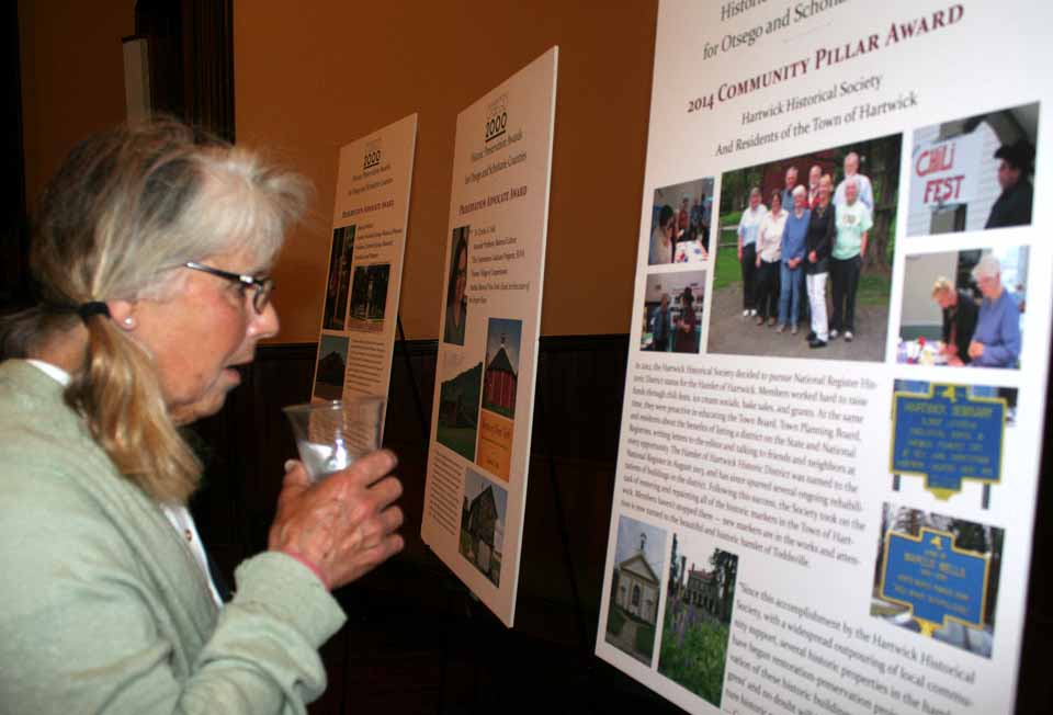 Jean Finch, Toddsville, examines the storyboard presenting the Hartwick Historical Association's recent accomplishment at Otsego 2000's Historical Preservation Awards ceremony Friday evening at the Upper Susquehanna Cultural Center, Milford.   The Hartwick society received the 2014 Community Pillar Award.  (Jim Kevlin/allotsego.com)