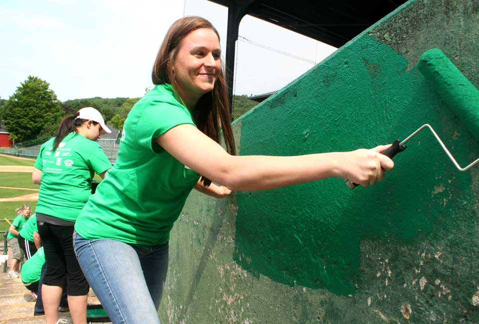 Ashlee Lansing, who handles sports bookings for the Holiday Inn, Albany, helps paint a bleacher wall at Doubleday Field this morning.  She was part of the Tourism Cares contingent.  (Jim Kevlin/allotsego.com)