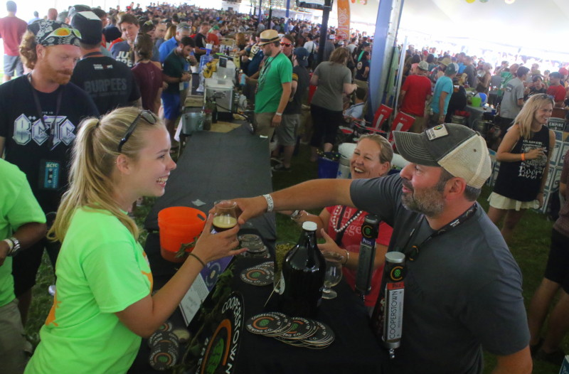 Event volunteer Emily Scribner, Rochester, left, gets a glass of beer from Ian and Jennifer Porto, who were manning the Cooperstown Brewing Co. tasting station at this weekend's Begian Festival at Ommegang Brewery. (Ian Austin/allotsego.com)