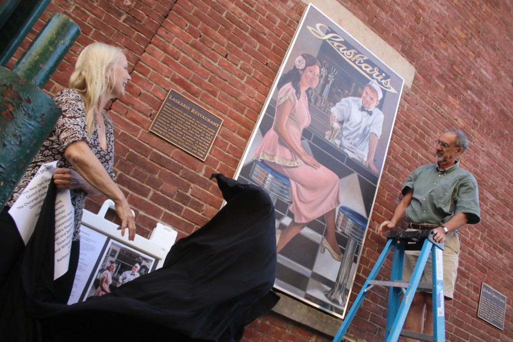 The Laskaris Mural, installed on the side of the Greater Oneonta Historical Society, was unveiled at 6pm today by artist Carol Mandigo and Bob Brzozowski. The mural is the second in a series tracing the history of businesses that have occupied 183 Main St. since the 1800's. (Ian Austin/ allotsego.com)