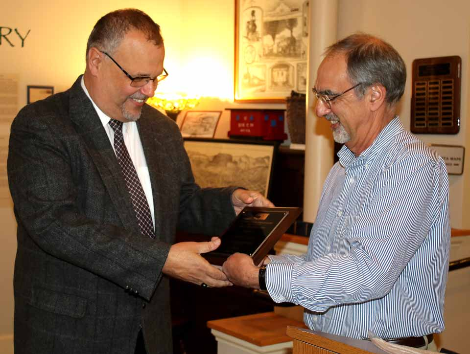 "Chuck D'Imperio, left, author of seven books on Upstate history and WDOS-FM host, receives the 20th Albert E. Morris Award for contributions to local history from Bob Brzozowski, executive director Greater Oneonta Historical Society, at a reception at the Oneonta History Center. In his remarks, D'Imperio recounted the close race between the Republican Morris, the city's first mayor, and Democrat George Gibbs. After a campaign that featured huge rallies and torch-light parade, Morris eked out a two-vote victory, ""or I would be receiving the George Gibbs Award."" Other recipients include Norma Hutman, longtime historical society president; Swart-Wilcox House mainstay Helen Reese, former Mayor ""Big Jim"" Lettis, Railroad Historian Jim Loudon, former Mayor Sam Nader and railroad buff Tony Mongillo, whose railroad lithographs will be features in a show that will open Feb. 1. (Jim Kevlin/AllOTSEGO.com)"