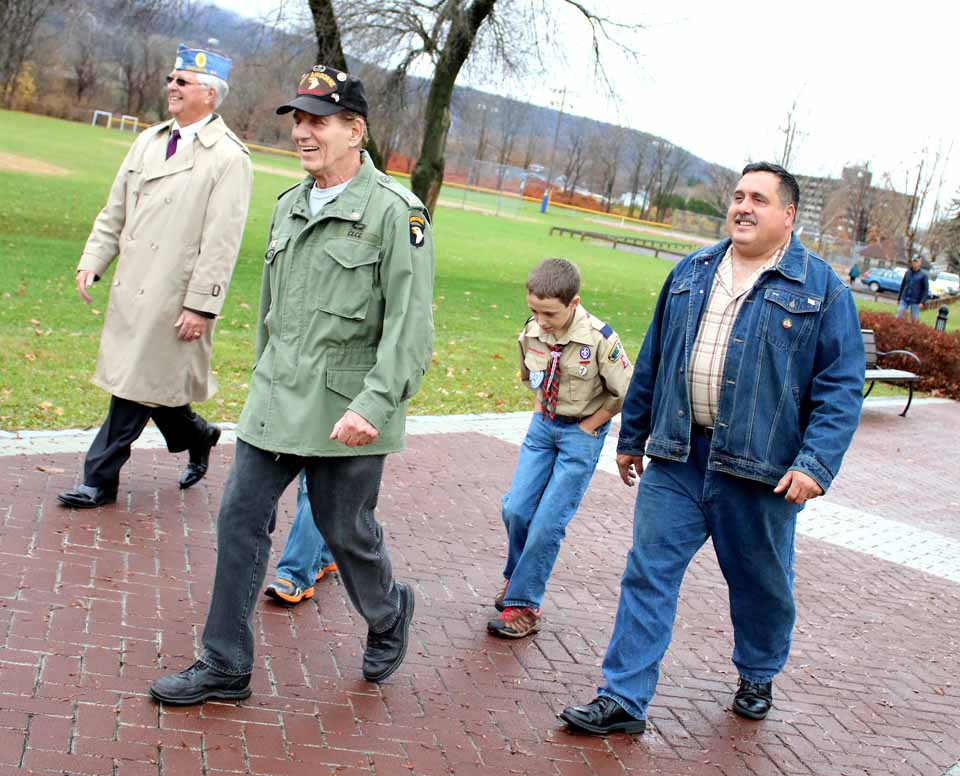 Les Grummens, Tony Cece, Aaron Pondolfino and Tom Pondolfino walk along the memorial walkway to the ceremony.