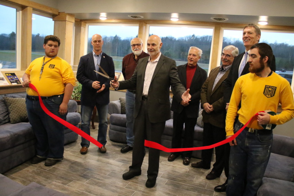 """After two years of construction of the new terminal at the Oneonta Airport is finally completed. Mayor Gary Herzig, flanked by OJC student Joe Henness, Len Carson, Jeff Back, Dennis Finn, Ed May, Chris Kuhn and OJC student Nate Morris, cuts the ribbon at the Oneonta Municipal Airport, where the milestone was celebrated this afternoon. In remarks beforehand, Kuhn praised his students' work; """"They did not disappoint. We've been involved with a lot of projects over the years, this has been the best so far."""" Mayor Herzig, who had lunch with former Mayor Sam Nader earlier today, recounted how Nader had considered the building of the airport the project he was most proud of. """"For years the airport languished, and was even given up for dead."""", said Herzig. """"But you have brought back this facility for Oneonta's future. You have done us a real service."""" Senator Jim Seward hailed the work and announced he has secured a $70,000 grant to help complete the work. """"First impressions mean a lot."""", said Seward. """"This terminal tells those who arrive in our community 'this is a great place to live, to visit and to work.'"""" Many cited the passion of current Airport Commissioner Dennis Finn, who worked at the airport in it's first days. """"I love this place and people who come here love it, too"""" (Ian Austin/AllOTSEGO.com)"""
