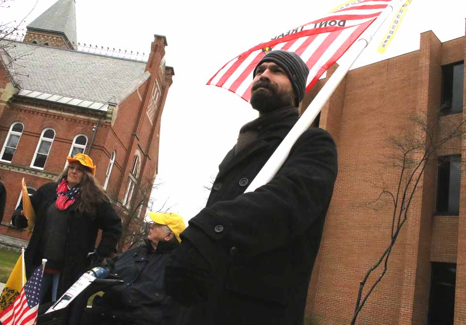 """Vicent Rasulo of East Patchogue, L.I., bears the """"Don't Tread on Me"""" flag at the tax protest underway at this hour in front of the County Office Building ,n Cooperstown. About 20 people are in attendance, including Marie Ajello, Richfield, and Bob Force, Gilbertsville, who lost their properties in the 2014 tax auction, despite offering to pay back taxes. At left is Judy Pepenella, also of Long Island, a founding board member of the Conservative Society for Action. In the middle is Jeanne Bridger, Town of Maryland (Jim Kevlin/AllOTSEGO.com)"""