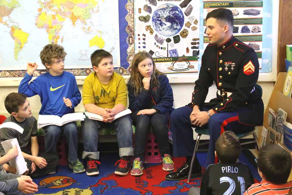 Back from deployment in Romania, Marine Jeremy Denmeade of Richfield Springs thanks pupils in Ann Szwejbka's third=grass class at Cooperstown Elementary School this afternoon.