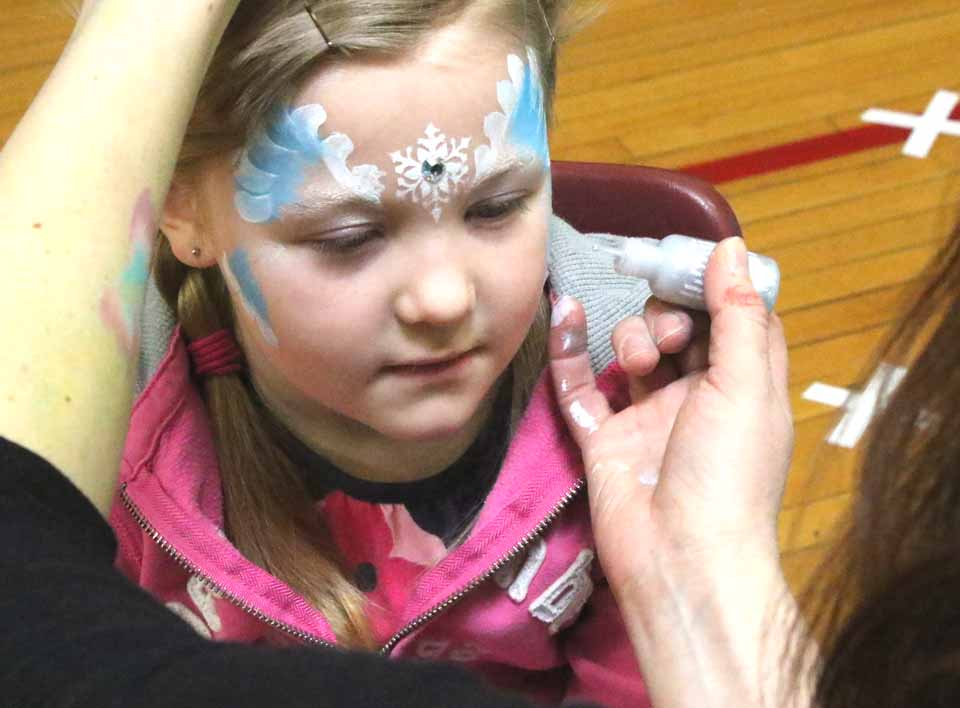 Allison Butts of Cooperstown, feels pretty, oh so pretty, as a final sequin is added to her cheek at the face-painting booth today at Cooperstown Central School's Bursey Gym. (Jim Kevlin/AllOTSEGO.com)
