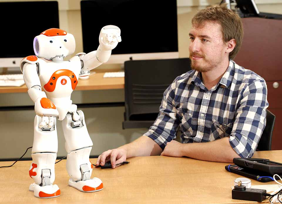 SUNY Oneonta studeny Mark Crosby interfaces with Ricky the Robot, who is helping develop communication skills of children with autism. (SUNY Oneonta photo)
