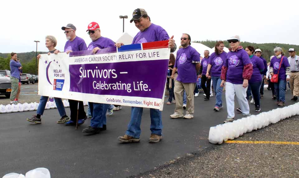 Holding the banner at today's Cooperstown/Northern Otsego Relay For life are, from right, survivors Ed Bellow and Jim Domion, both of Richfield Springs, and Michael Hall, West Oneonta. At the far end is Helen Gregory, executive director of the local chapter of the American Cancer Society. The Relay continues until 10 p.m. at Cooperstown Dreams Park in Hartwick Seminary. (Jim Kevlin/AllOTSEGO.com)