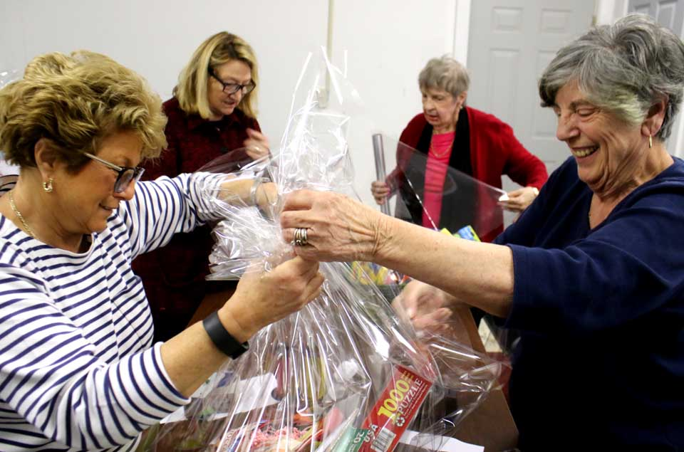 "Cooperstown Rotarians – from left, Marge Landers, Margaret Savoie, Karen Cadwalader and Joan Badgley – pack one of 65 baskets of goodies that will be auctioned off at 5 p.m. Friday at 1 Railroad Ave., Cooperstown, a ""warm-up"" to Saturday's ""Spring Fling."" Gary Kuch and Bob Schlather will be auctioneers. Food and refreshments available. The auction is a preview to Saturday's main in event – from noon to 5 p.m., a festival of music, food, games and other fun in the middle of Railroad Avenue. Highlights include the Spurbeck's Market 75th anniversary, and samples provided by the Beverage Trail. (Jim Kevlin/AllOTSEGO.com)"