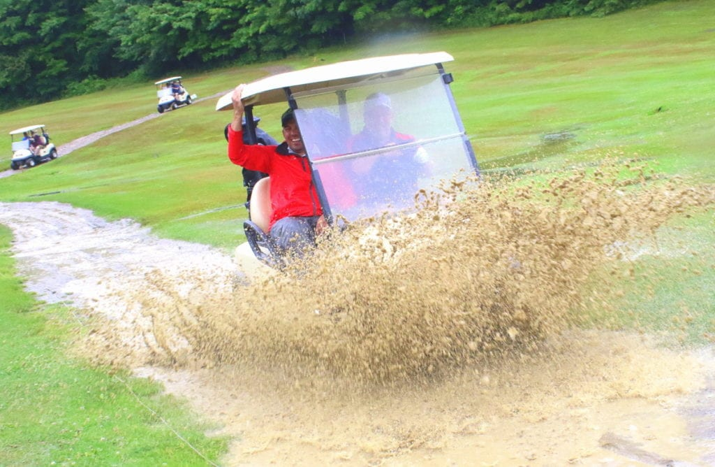 Fred Schneider, Cooperstown, drives through a puddle on the Colonial Ridge Golf Course while partner Sean Campbell holds on for dear life. But despite the storm that delayed tee-off time two hours, the game worth the wait, part of the Friends Helping Friends benefit tournament to raise money for for cancer patients Art Boden and David Selover. (Ian Austin/AllOTSEGO.com)