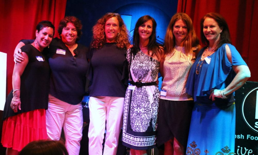 Aida Rogers, Colleen Andrew, Cathy Deleski, Melinda Murdock, Terry Basdakis and Julia Goff pose for a photo on the stage at the B-Side Ballroom this evening where 100 Women Who Care Otsego donated $7,200 to OFO's Violence Intervention program. The group, now in it's fourth year, selects three charity organizations at random from selections offered by members. Representatives must then pitch their 501c3 program in front of the group for a chance to be chosen to receive the funds collected that year. Past winners have included The Lord's Table, Family Services and Athelas Therapeutic Riding. OFO's violence Intervention Program currently employs 12 people and offers emergency shelter, counseling, crime victim compensation, medical and crime accompaniment relief, and group counseling; all for free. In the past year they have served 63 women and 19 children, given 1900 counseling sessions, and taken 894 calls through their 24 hour hotline. (Ian Austin/AllOTSEGO.com