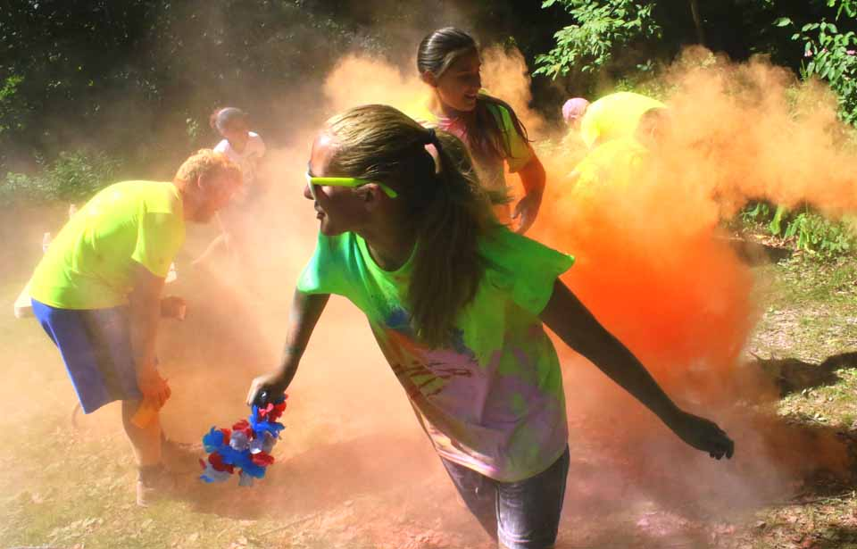 Montana Miller and Elizabeth Cleveland, Oneonta, emerge from a cloud of orange smoke as they pass a color station in the 1st LEAF color Run, held throughout Neawah Park this morning before the parade.
