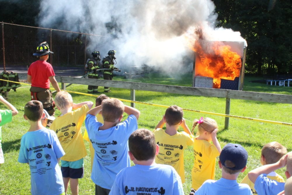 "Participants in the YMCA's Junior Firefighter safety course, were treated to a live burn demonstration this morning by the Oneonta Fire Dept. ""A fire doubles in size every 30 seconds."" explains Don Tubia, left, Oneonta, as the children begin to feel the intense heat from the blaze. In the background, Dan Alley and Chuck Barringer prepare to douse the blaze. Over the last two days, participants in the program learned fire safety precautions, met fire dogs, ran fire drills, explored a medevac helicopter, and got up close and personal with Oneonta Fire fighters. The day ended with awards, ice cream and of course, a refreshing dousing by the fire hose. The program is now in its 11th year. (Ian Austin/AllOTSEGO.com)"