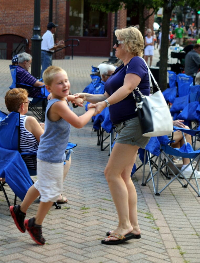 Kim Snyder, Oneonta, and her son Nathan, dance to the classic rock sounds of Off The Record, who was preforming in Muller Plaza during the Cruise In at this evening's First Friday. Main st. was closed off and filled with classic cars and food, including brownie sundaes at the Greater Oneonta Historical Society. (Ian Ausin/AllOTSEGO.com