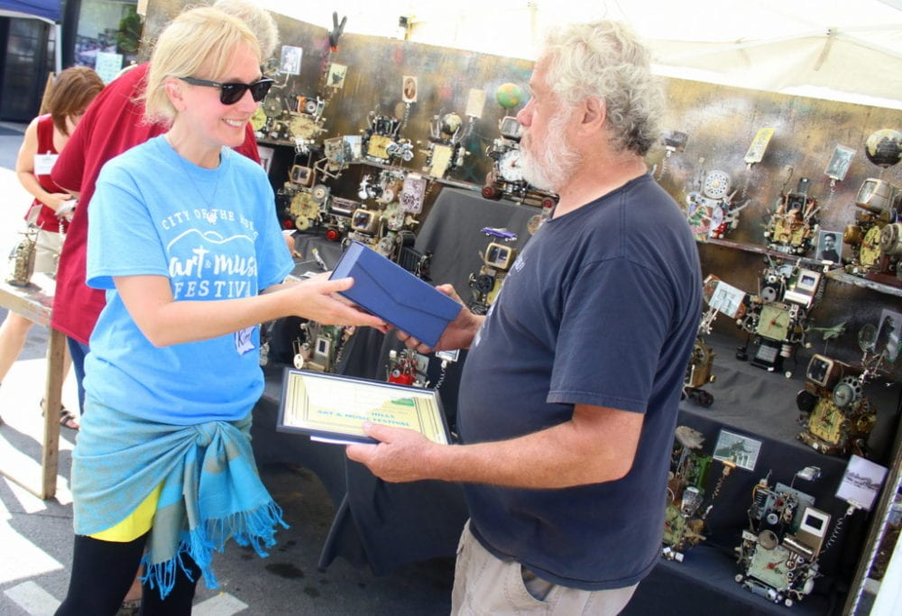 Kim Condon, Oneonta, hands Richard Birkett, Otego, the Best in Show Award for his intricate Fantasty Clocks. Each piece is meticulously assembled from hundreds of objects including toys, gears, hinges, pipes, slide viewers, old photographs, springs and more. Birkett was one of many artists who lined Main St. this afternoon for the 14th Annual City of the Hills Art & Music Festival this afternoon. Shoppers could browse pottery, jewlery, paintings, clothing and photography while enjoying readings from area authors, live music, belly-dancing, and children's activities. (Ian Austin/AllOTSEGO.com)