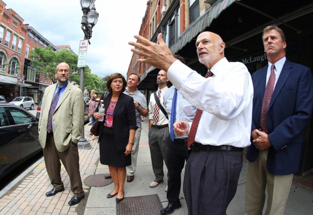 """Following his presentation at the Mohawk Valley Regional Economic Development Council in the Hunt Union Ballroom, Mayor Gary Herzig led a walking tour of Main St. Oneonta and Market st. to MVREDC members. Here, executive director of Sculpture Space Tom Montan, Department of State Revitalization Specialist Julie Sweet, councilman Joe Ficano, STANTEC consultant Jamie Ethier and councilman Russ Southard listen as Herzig tells the history of the former Bresees building and it's restoration into Klugo's Park Place. """"Integrated housing like this is key."""" said Herzig. """"Main st. and Market St.) need to compliment each other."""" (Ian Austin/AllOTSEGO.com)"""