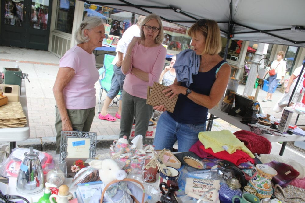 Bobbi Frazier, Michele Townsend and Roxanne Murry look over the goods at the P.E.O booth at the Grand and Glorious Garage sale this morning. The event, now in it's 37th year, is organized by the Catskill Choral Society. It was bargains galore as shoppers flooded Main Street in search of treasures. Mayor Gary Herzig made the rounds with Senate hopeful Zephyr Teachout who introduced herself to vendors and shoppers. The Community Concert Band gave a performance around mid day, and there was no shortage of foo selections with everything from spicy sausages, walking tacos and local produce from the Farmer's Market. (Ian Austin/AllOTSEGO.com)