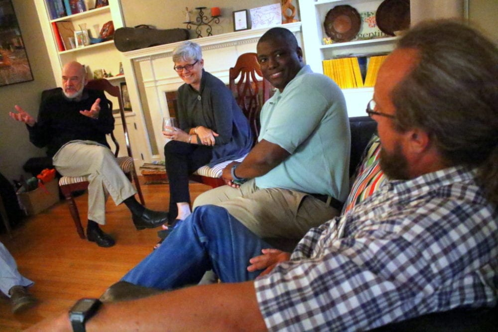 """Ed Lentz, Oneonta, right, and Paul and Sarah Patterson, Oneonta, left, talk about the issues with Jermaine Bagnall-Graham, center, Sherburne, at a meet and greet hosted at the home of Daniel Butterman, a OCDC committee member. About a dozen people attended to discuss topics ranging from renewable energies, cell and internet services, taxes and keeping local businesses.  Bagnall-Graham is only the 4th candidate to run against Sen. Jim Seward, R-Milford, in his 30 year term. """"I want to do what is best for the residents."""" said Bagnall-Graham. """"I want to debate (Seward) on the issues, but so far he has not responded to me."""" (Ian Austin/AllOTSEGO.com)"""