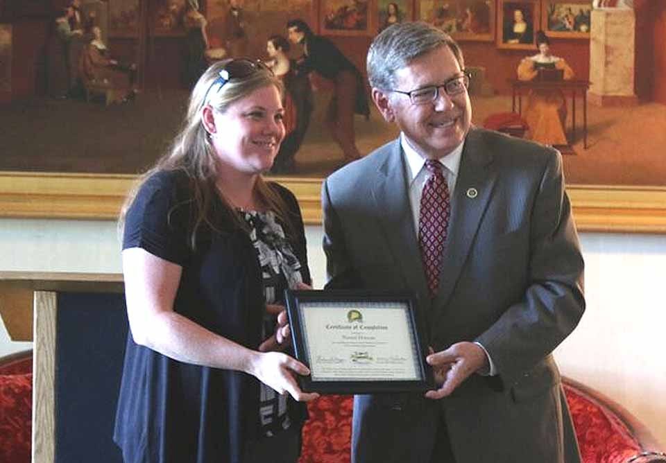 """Naomi Duncan, manager of Community Bank's Cooperstown branches, receives a certificate of completing the Otsego County Chamber of Commerce's Leadership Otsego program from state Sen. Jim Seward, R-Milford.   This year's class completed the program, which introduces them to key businesses, governmental entities and non-profits, in a ceremony Wednesday, Sept. 21, at the Hyde Hall National Historic Landmark on Otsego Lake.  Behind Duncan and Seward is Hyde Hall's full-size replica of Samuel B. Morse's """"The Gallery of the Louvre"""";  the original, acquired by George Hyde Hall, the mansion's original owner, was hung in that space."""