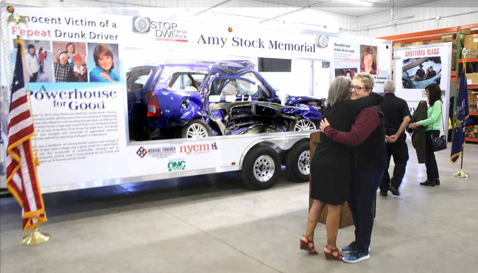 Kim Robinson of Prolifiq Signs, which did the graphics on the Amy Stock Memorial trailer, hugs Amy's sister Eileen Anania, who led the effort to turn a tragedy into teaching moments, as Tuesday dedication ceremony was about to begin. (Jim Kevlin/AllOTSEGO.com)