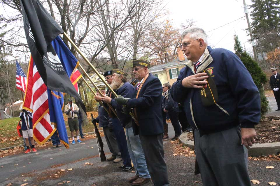 The color guard from the Cooperstown Vets Club that led this morning's parade included, from right, Dick Hanson, John Aurelio, Lee Whinney and David Sanford. As old Stars & Stripes were retired in flames, a light rain fell on the ceremony in from of the Doughboy Statue at lower Pine Boulevard, across from The Otesaga. (Jim Kevlin/AllOTSEGO.com)