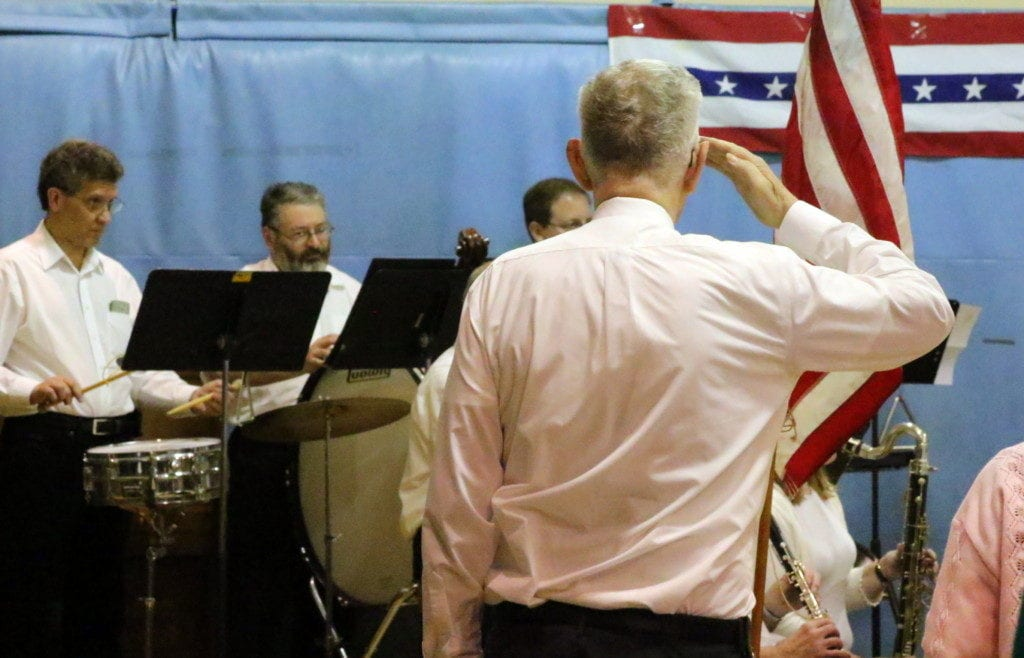 """Bradley Osborne, Oneonta, who served in the U.S. Army and Airforce, salutes the flag as Oneonta Community Concert Band plays """"Star Spangled Banner"""" at St, Mary's this evening. The song was one of many military-themed selections the band has chosen for their 17th Annual Salute To Veterans Concert held this afternoon. Each branch of the military was recognized and honored. Cake, coffee and conversation closed out the event. (Ian Austin/AllOTSEGO.com)"""