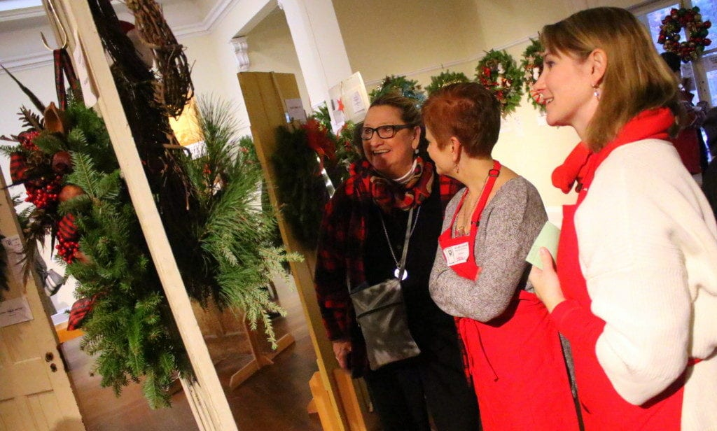 A cheerful Margaret Savoie, left, got in the holiday spirit with her daughter, Jackie, as they bid on wreathes at Adorn-A-Door Wreath Festival this afternoon at the Cooperstown Art Association. With them, center, is volunteer Tara Santello. The annual event, which invites visitors to bid on handmade wreathes from local artists & businesses, raises money for art scholarships. (Ian Austin/AllOTSEGO.com)