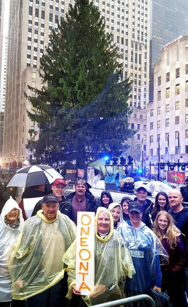 A contingent from Oneonta arrives at Rockefeller Plaza a few minutes ago, looking forward to the lighting of the Eichler family's 95-foot-tall blue spruce at 8:55 this evening. From left are Linda Rae-Nichols, Ted Gaisford, Darren Gaisford, Todd Foreman, Emmy Gaisford (with sign), Sue Gillette, June Sheehan, Tracy Gaisford, Greg Krikorian and his two daughters, Bridget and Claire, and Brian Gillette. The contingent rode one of Eastern Travel's chartered buses from the City of the Hills to the Big Apple today. (Ian Austin/AllOTSEGO.com)