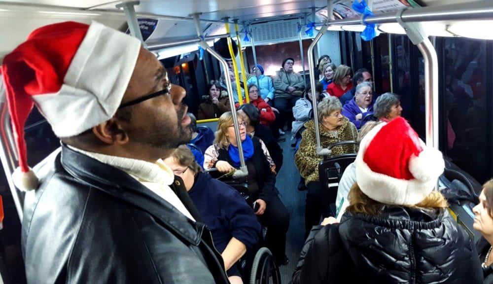If you saw a packed OPT bus making it's way around residential streets this evening, rest assured they weren't lost! The bus, driven by Paul Patterson, was taking residents of Nader Towers on a city-wide tour of Christmas lights. D.J. Wooden and Julie Pitell, seen in the foreground, lent their vocal talents by singing Christmas songs with the riders to get everyone in the spirit. The event, organized by Carla Balnis, was so popular that she intends to expand it for next year to include rides for Academy Arms and Peaceful Flatts. (Ian Austin/AllOTSEGO.com)