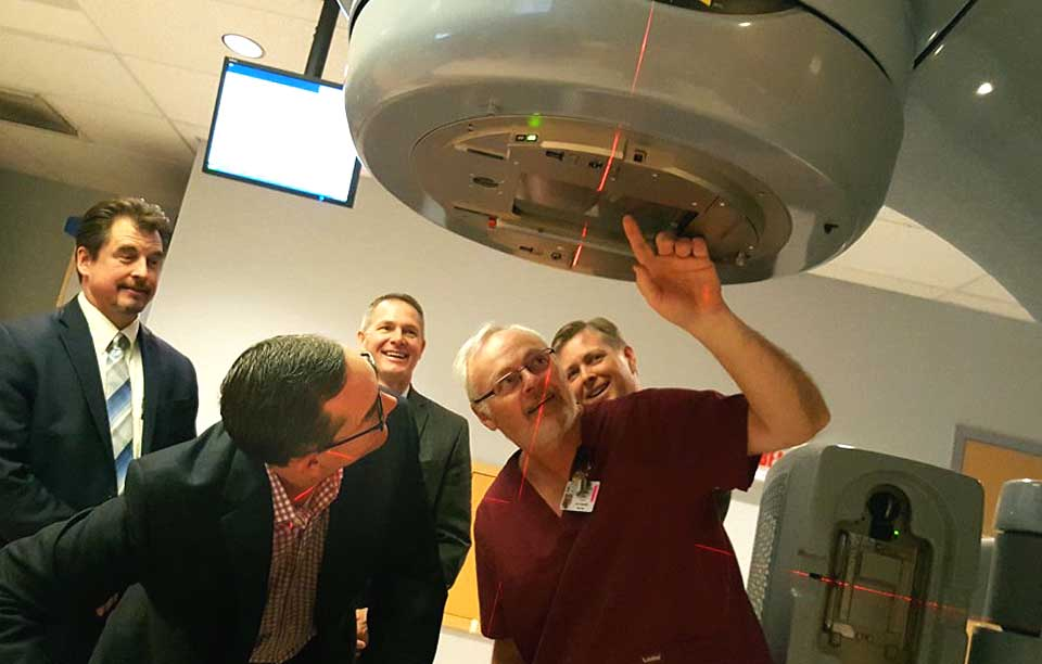 "Mark Tryniski, left, Community Bank president/CEO, and Radiation Therapist Roy Doremus, right, look into the eye of the Foxcare Cancer Treatment Center's linear accelerator.  Tryniski was at FoxCare today to deliver the final $20,000 payment of a $100,000 pledge the bank made toward the 2012 purchase of the advanced apparatus, which more accurately pinpoints tumors and treats them, avoiding the need for more intense radiation.  Behind them are, from left, Jeff Lord, Commercial Banking team leader, Joe Sutaris, bank vice president, and Jeff Joyner, Fox Hospital president.   ""These cutting-edge treatments are changing the landscape of cancer treatment, making radiation therapy an open for many more patients than ever before,"" said Joyner.   He also thanked the Dewar and Robinson Broadhurst foundation for helping cover the accelerator's price.  (Ian Austin/AllOTSEGO.com)"