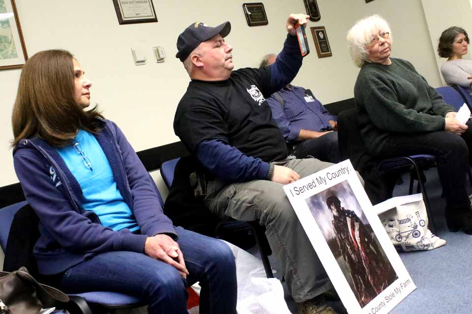 With a protest sign between his knees, Bob Force records this morning's county board meeting in Cooperstown. At right is Marie Ajello. (Jim Kevlin/AllOTSEGO.com)