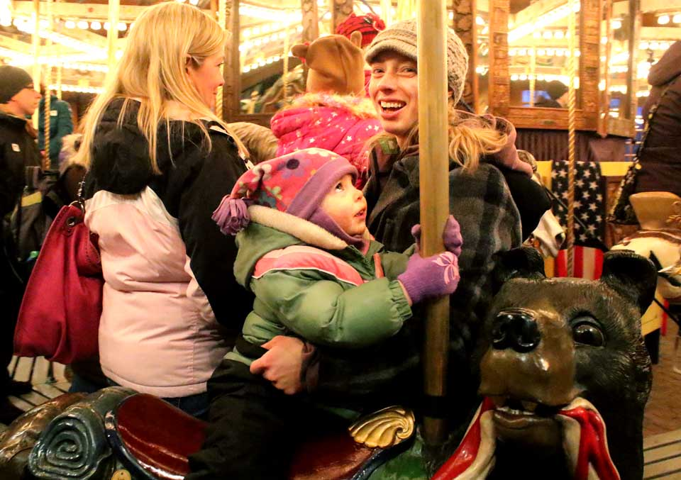 Nini Brackett, 2, of Fort Plain, experience the awe of the Empire State Carousel at today's Candlelight Evening at The Farmers' Museum in Cooperstown. With her is mom Cassy. Compare to last year's 40s temperature, everyone seemed to agree that this year's inch of fresh snow and temperatures in the 20s were just right. (Jim Kevlin/AllOTSEGO.com)