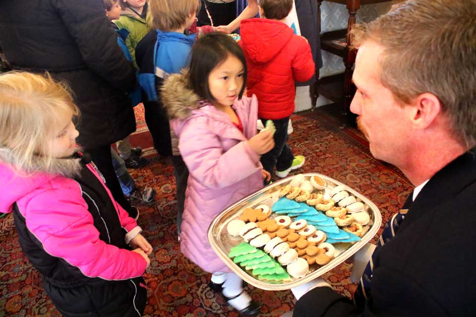 The Otesaga's Robbie Huntington hands out cookies to CCS pupils who, as is traditional, sang Chrismas carols to the Cooperstown Rotary Club at its luncheon meeting today.  (Jim Kevlin/AllOTSEGO.com)