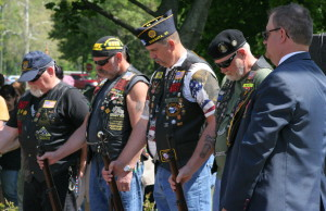 "Jim Williams, Terry Harkenreader, Gary Ballard and Emerson Horth, members of the American Legion Firing Squad, bow their heads alongside Jim Hawver as ""Taps"" is played."