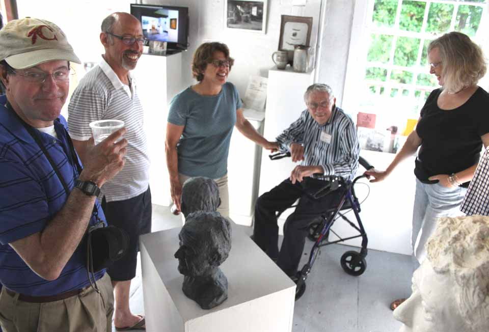 "Sculptor Alex Bauer, 92 and a Cooperstown resident for six years, was honored this evening at the opening of the Smithy Pioneer Gallery's first show of the season, ""On Closer Inspection"" At left is his son, Dr. Mike Bauer, and to the sculptor's right is his daughter Jane.   Bauer's sculpture, and the works of six artists, will be on view through June 29. (Jim Kevlin/allotsego.com)"