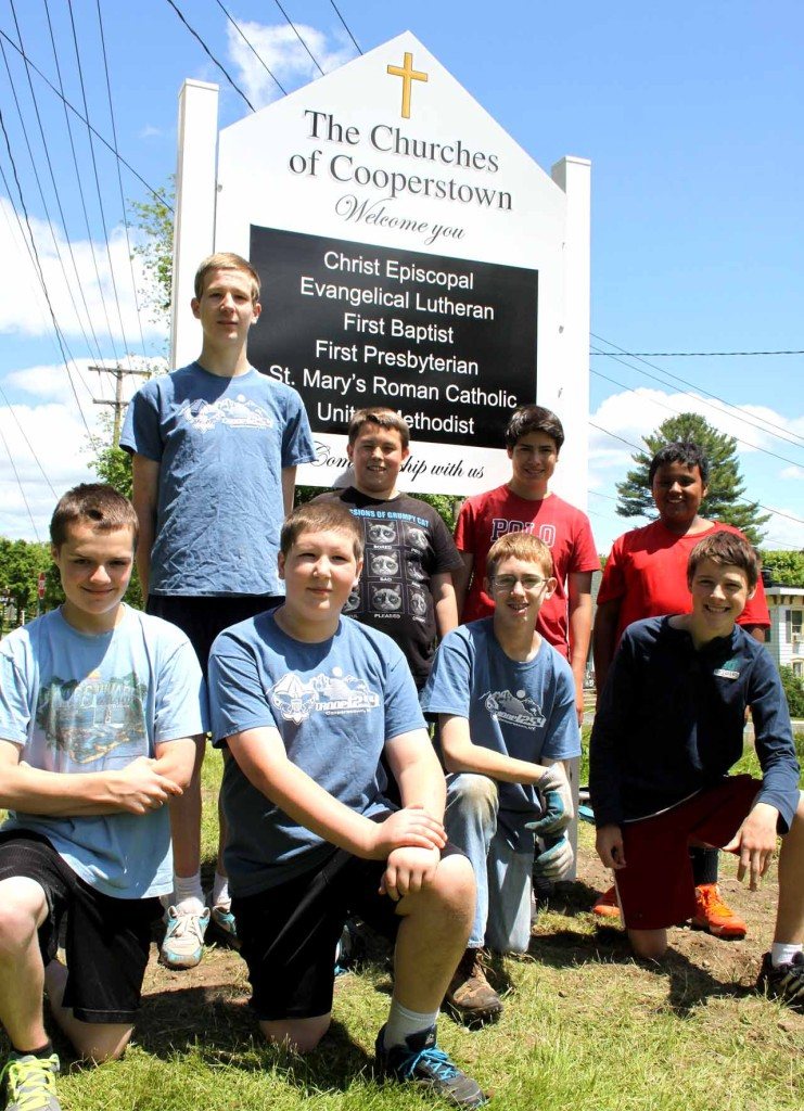 Eagle Scout candidate Charles Gannon, standing at left, obtained the help of his fellow Troop 1254 scouts for signs at the two Route 28 entrances to the village welcoming visitors to Cooperstown's churches.   Others standing, from left, are Tim Walker, Daniel Rudloff and Nathaniel Miller.  Front row, from left, are Matthew Hulse,  Eric Deysenroth, Leo Gannon and Steve Ratliff.  Also assisting were Josh Briggs and Anthony Birch.  (Jim Kevlin/allotsego.com)