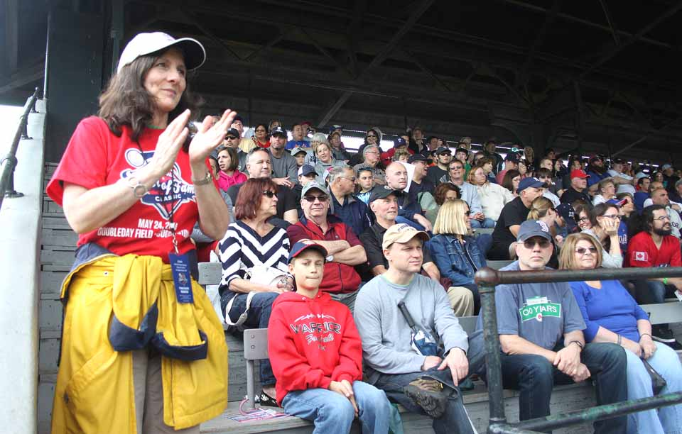 """Usher Penny Gentile takes time out from her duties to applaud the action on the field in front of a packed Doubleday Field grandstand.  """"The stadium looks full to me,"""" said Ken Meifer, Hall VP/development and vice president of the Destination Marketing Corp. of Otsego County."""