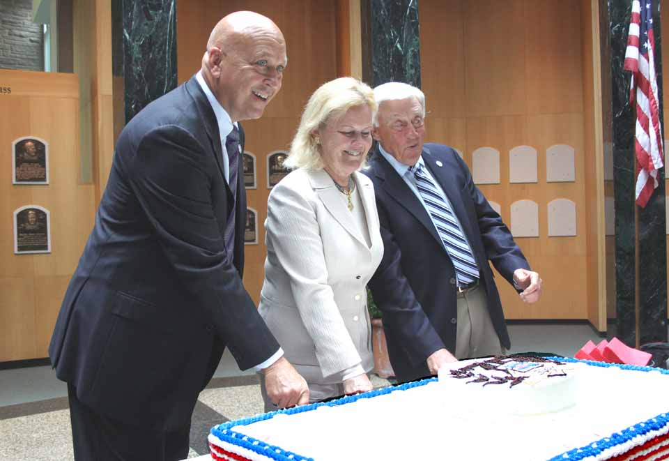 National Baseball Hall of Fame board chairman Jane Forbes Clark, flanked by Hall of Famers Cal Ripken Jr. and Phil Niekro, cut the birthday cake marking today's 75th anniversary of the Hall's first Induction in 1939.  The Hall of Plaques was packed with fans and wellwishers.  (Jim Kevlin/allotsego.com)