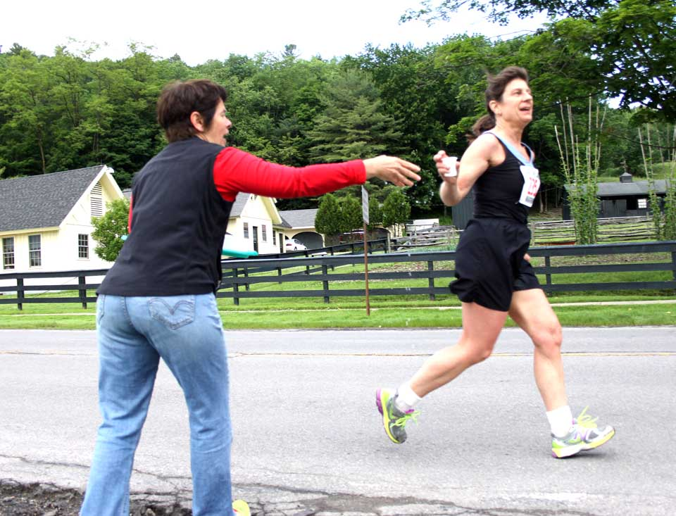 Runner Nancy Potter of Cooperstown takes a cup of water at the first refreshment station from Meg Kiernan, who was manning a table by Leatherstocking Golf Course, courtesy of The Otesaga.