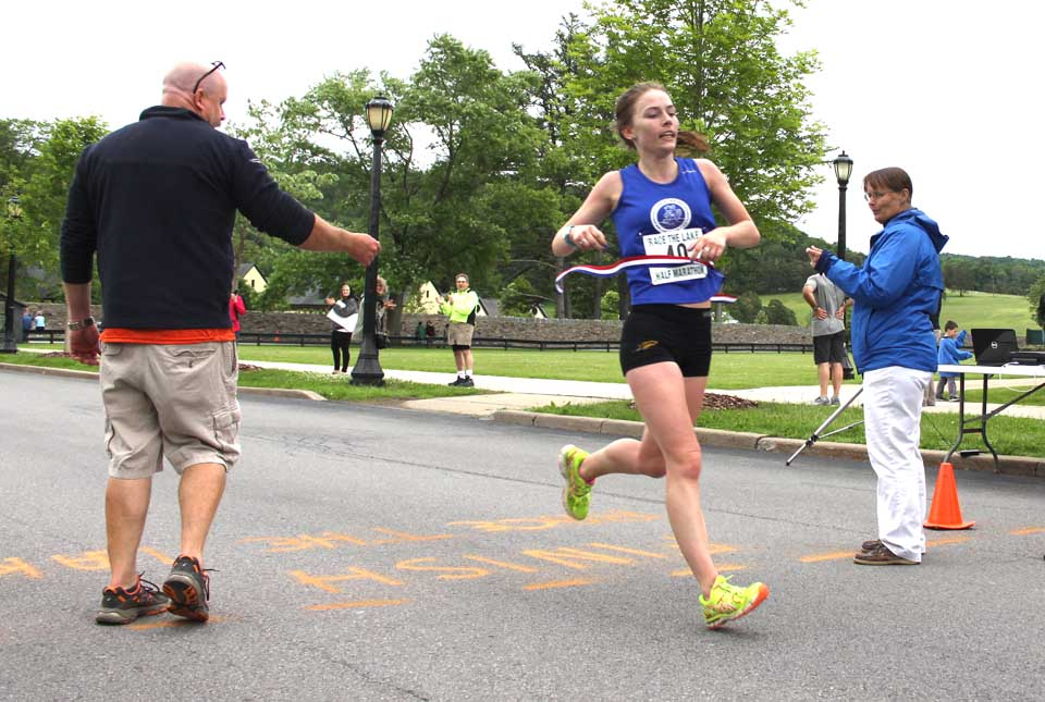 Dierdre Dwyer of Poughkeepsie and Cooperstown breaks the tape, the winner of today's half-marathon.