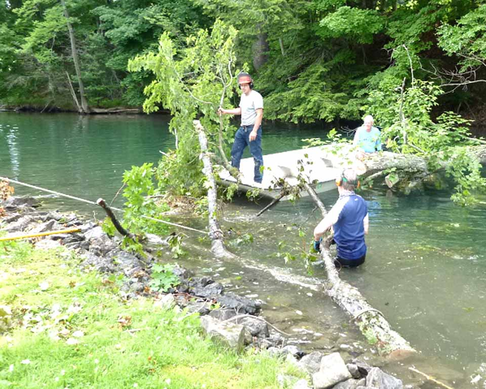 The Susquehanna River just south of its source in Otsego Lake is clear again after neighbors, including Dreams Park owner Lou Presutti Jr., participated in removing a tree trunk that had fallen from Presutti's property a week ago  In photo, from left, neighbors Josh Howard, Chip Northrup and Lang Keith removed the trunk to the Thompson Inflection Point.  Firewood available for the asking at 15 River St.  At first, Presutti obtained counsel, and neighbors feared there would be some obstacle to reopening navigation.