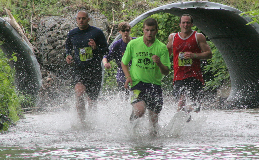 Through the woods and through the river, Marc Weinmuller, Lee Ferarra, Garret Decker and Joshua Michalski barrel their way up the mill race creek into the last leg of the Tuff E Nuff on Friday morning during the competitive wave.